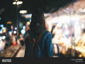 Woman on city street at night