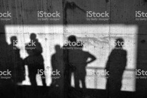 Men shadows on the concrete wall.
