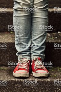 Image of legs in jeans and feet in red sneakers.
