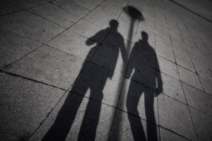 Shadow silhouettes of two men holding hands