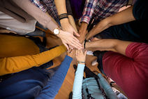 Image of a diverse group of people with hands forming a circle
