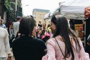 Women talking as they walk through a crowd