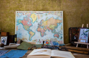 Image of world map and desk with book and supplies on it