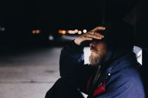 A man sitting on the street at night